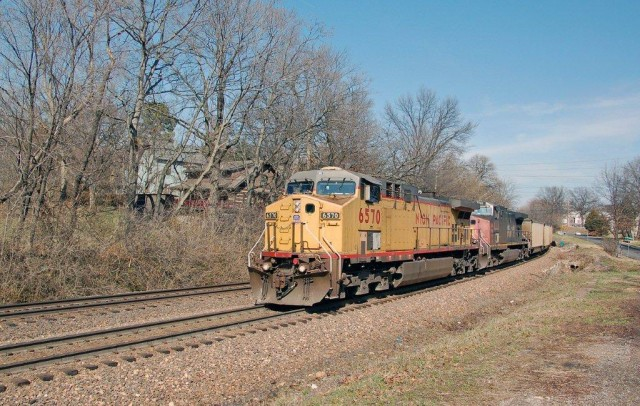 "Geyer Road in Kirkwood is the location where we find a UP AC 44CW headed west with coal empties on ""reverse iron""; the second unit is still in its Southern Pacific paint. This spot is just west of the Kirkwood Station."