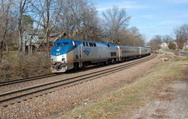 Amtrak's afternoon train to Kansas City has just departed Kirkwood Station, which is just behind the overhead bridge to the rear of the train.