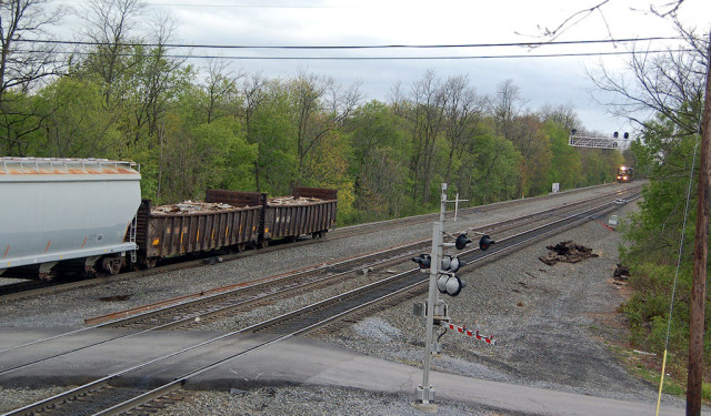 Note the helper set following closely behind a slow-moving east bound freight downward at the brick yard.