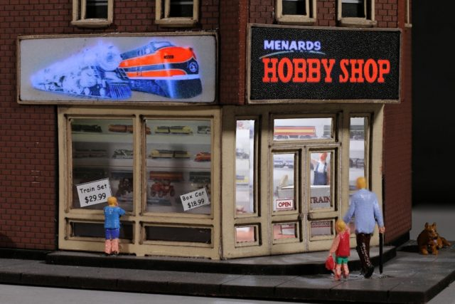 The Menard's Hobby Shop features two flashing signs and an illuminated interior.
