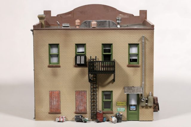 The rear wall features a fire escape, electric meter, and trash and paint cans.