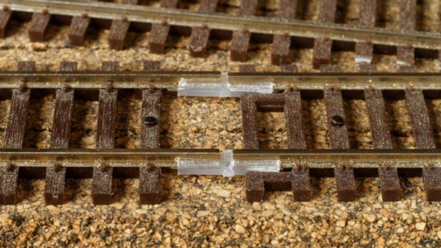 Here's a typical joint between flex-track (on the left) and sectional track (on right). A tie has been removed from the flex-track to allow room for the insulated rail joiners. Note that a hole was drilled in the flex-track last tie and a track nail added to ensure alignment. The missing tie will need to be added back before ballasting.