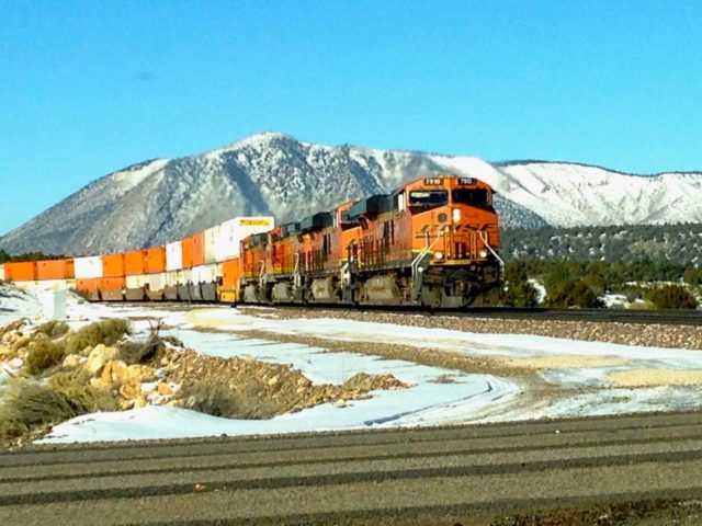 "The ultimate of ""grab"" shots, taken with my cell phone through the windshield when this BNSF stack train appeared just east of Flagstaff, AZ. Those are the Eisenhower peaks (12,000+ feet) in the background."