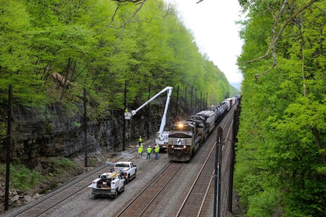 NS eastbound freight creeps past workers fixing a broken slide fence in a deep cut at Cassandra, Pennsylvania. When wires on the fence are broken by rocks or large chunks of ice falling to the track, a red stop signal is automatically displayed to prevent rail accidents. This is the old Pennsylvania Line; the fourth track was where the trucks are positioned. This is about 10 miles west of the Horseshoe Curve.