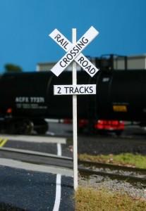 The scratchbuilt railroad crossing signs look great.