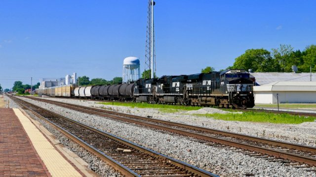 NS has just crossed the CN by the plant seen in the background, and is on its way from Louisville to St. Louis. Less than a mile ahead, it will veer off to the west and on to St. Louis. Tracks in the foreground belong to Canadian National.